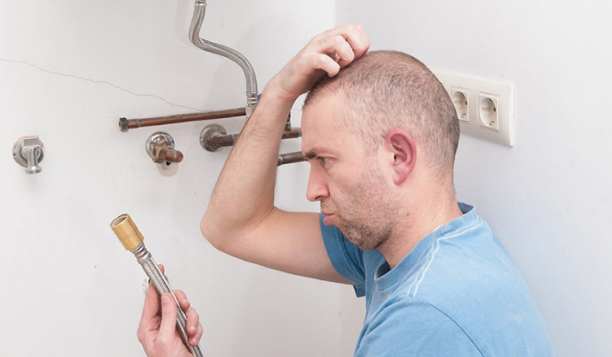 Man scratching head looking at hot water system part
