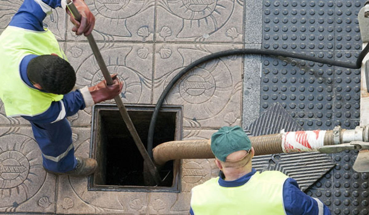 Two Plumbing Central men working hard to water blast a drain hole
